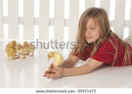 Girl laying with ducklings