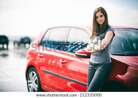 Girl leaning against a car - stock photo