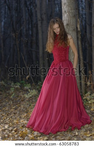 girl leaning against a tree in the twilight forest - stock photo