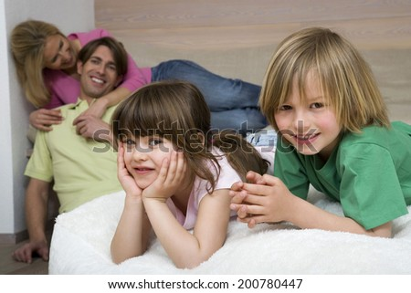 Girl leaning chin on hands boy lying next to her smiling parents in background
