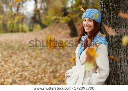 girl leaning on a huge tree in the autumn forest, in warm clothes, smiling and posing. Falling leaves also captured.  - stock photo