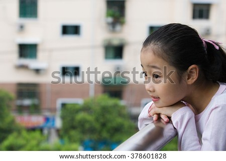 Girl leaning on a railing - stock photo