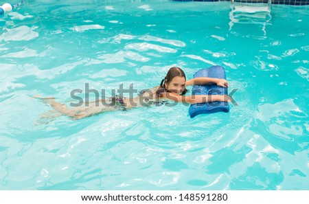 Girl learning to swim with board in the swimming pool