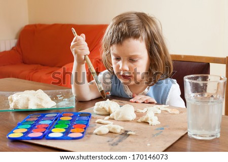 Girl learns to paint dough figurines in the room