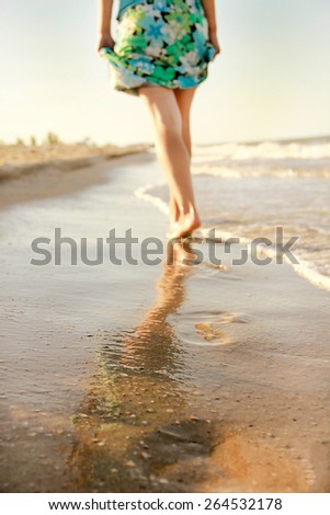 Girl leaves footprints in the sand - stock photo