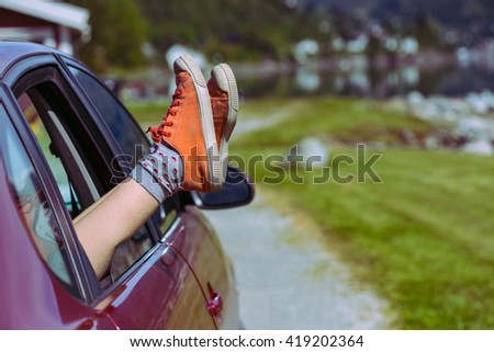 Girl legs in bright sneakers sticking out of the car, norway - stock photo