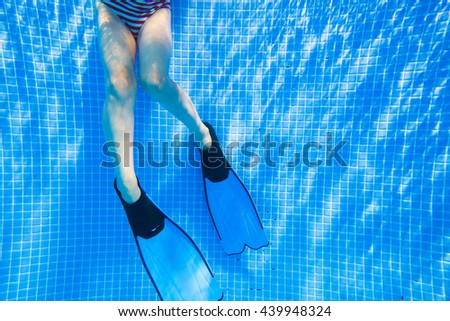 Girl legs in flippers under water in the pool - stock photo