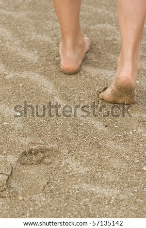Girl legs in sand near sea, vacation abstract.