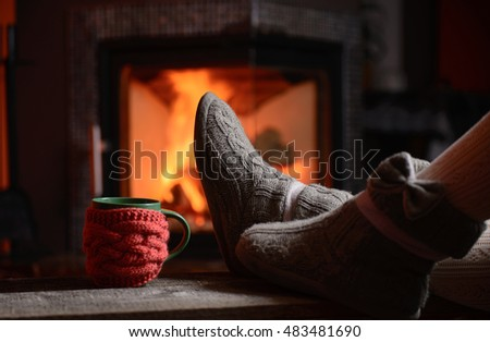 Girl legs in socks near the fireplace with a cup