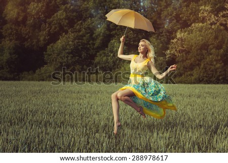 Girl levitates over the green field on the umbrella. She is wearing a nice summer dress.