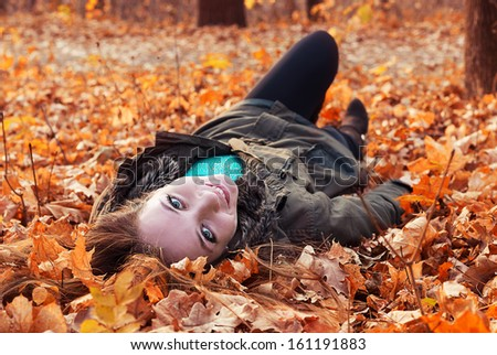 girl lies autumn yellow leaves of the trees
