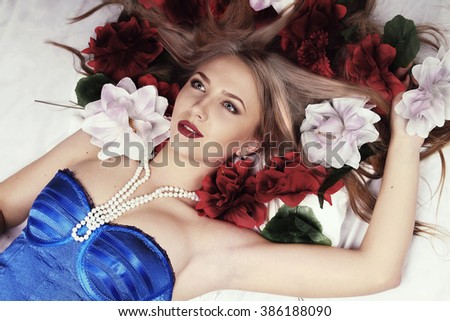 Girl lies in bed surrounded by flowers