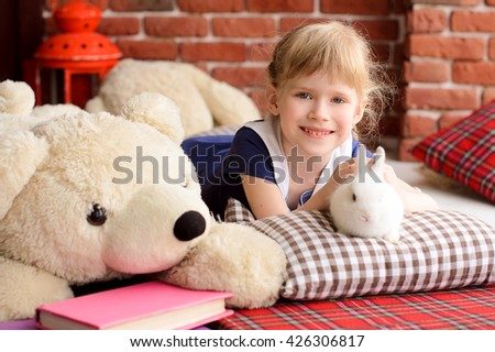 girl lies on a bed with a white rabbit, next to the white teddybear