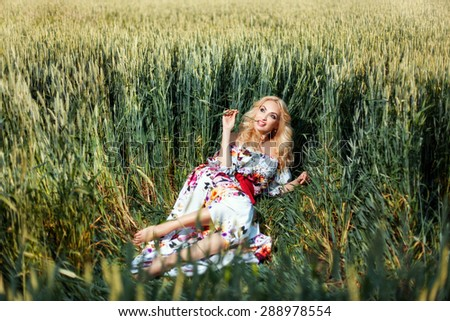 Girl lies on a rumpled grass on the field. She keeps flirting ears of corn mouth. - stock photo