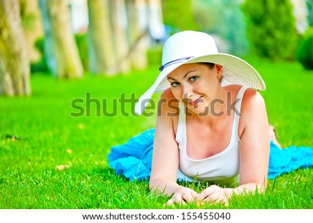 girl lies on the grass and looking at the camera - stock photo
