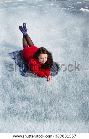 Girl lies on the ice of Lake Baikal