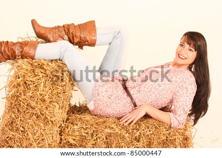 Girl lies with Western fashion on several straw bale /Country Girl - stock photo