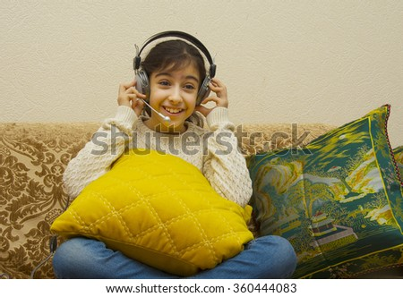 Girl listening music in headphones while sitting on sofa in room