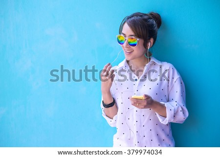 Girl listening music with headphones from a smart phone with Happy and relaxed Color Background - stock photo