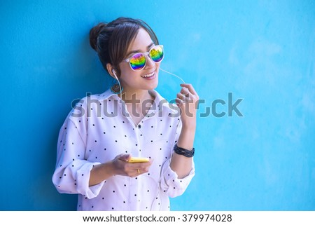Girl listening music with headphones from a smart phone with Happy and relaxed Colourful Background - stock photo
