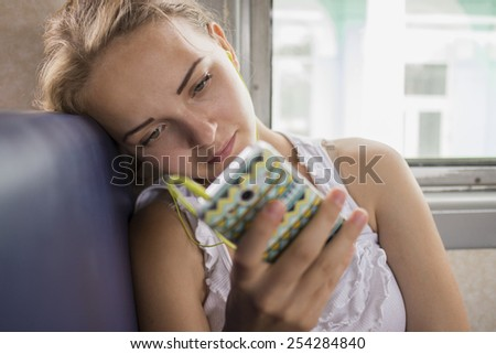 Girl listening to music, sitting by the window in commuter train  - stock photo