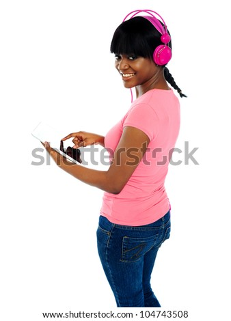 Girl listening to music via portable tablet. Enjoying herself - stock photo