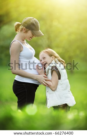Girl listening to pregnant mother's belly. Outdoor in park, shallow DOF. - stock photo