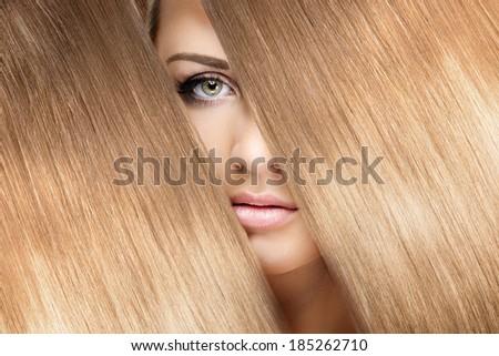 girl look through shining shiny blonde hair - stock photo