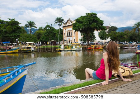 girl looking a the Paraty bay sitting on a quay