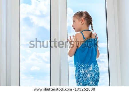 Girl looking at blue sky through window, copyspace - stock photo