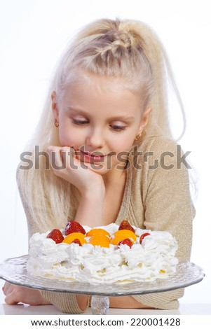 Girl looking at cake on white background. - stock photo