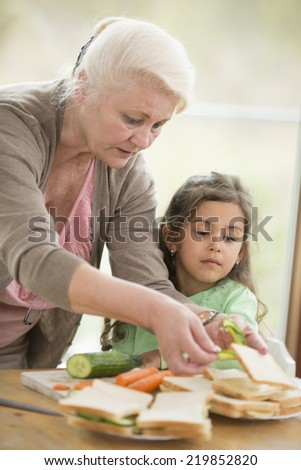 Girl looking at grandmother preparing sandwiches at home - stock photo