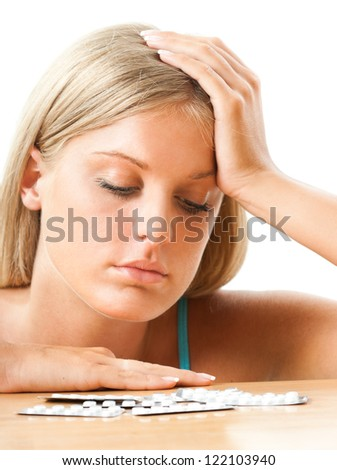 Girl looking at pills on the table,Taking pills - stock photo
