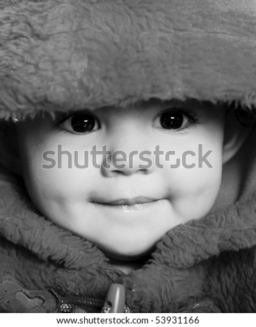 Girl looking at the camera and smiling with hood. Black and white image
