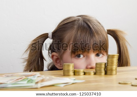 Girl looking at towers of money - stock photo