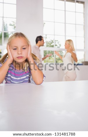 Girl looking despressed in front of fighting parents in the kitchen - stock photo