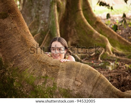 Girl looking from behind roots of the Moreton Bay fig tree