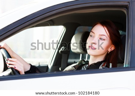 Girl looking in rear view mirror - stock photo