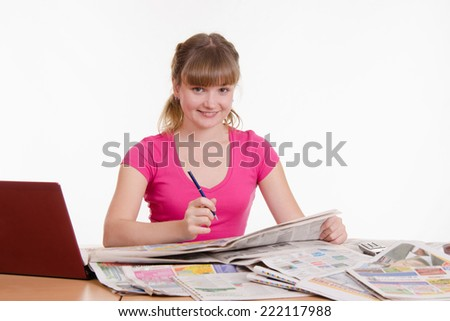 Girl looking in the newspaper classifieds - stock photo