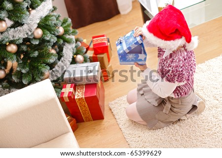 Girl looking inside an empty gift box in front of decorated christmas tree - stock photo