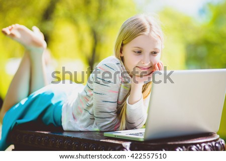 girl looking laptop lying on the bench at park outdoor - stock photo
