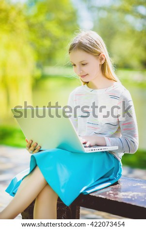 girl looking laptop sitting on the bench at park outdoor - stock photo