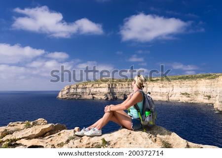 Girl looking on coast line near Azure Window on Gozo Island, Malta - stock photo
