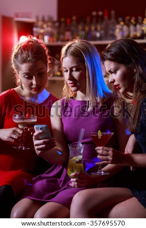 Girl looking on selfie with friends in club