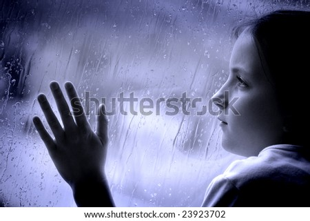 Girl looking out window on a rainy day