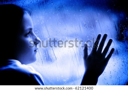 Girl looking out window on a rainy day - stock photo