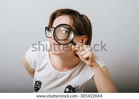 girl looking through a magnifying glass - stock photo
