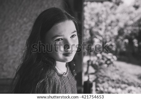 Girl looking through a window. Black and white portrait