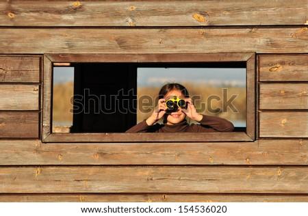 Girl looking through binoculars - stock photo