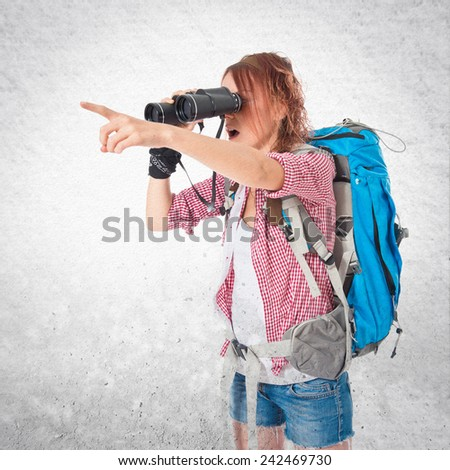 girl looking through binoculars over textured background - stock photo